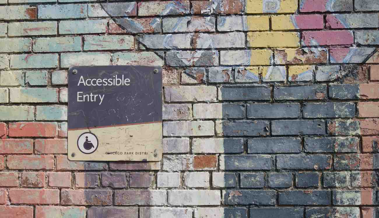 """Colorful brick wall with a sign saying """"accessible entry"""""""